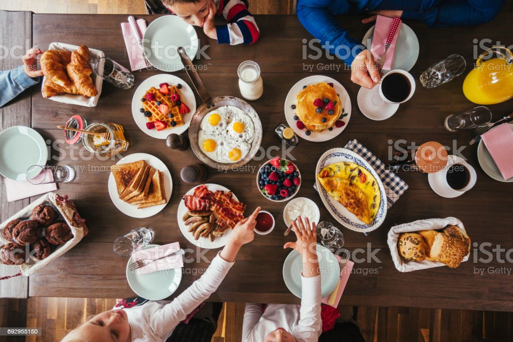 Young Family Having Breakfast with Eggs, Bacon, Yogurt with Fresh Fruits stock photo