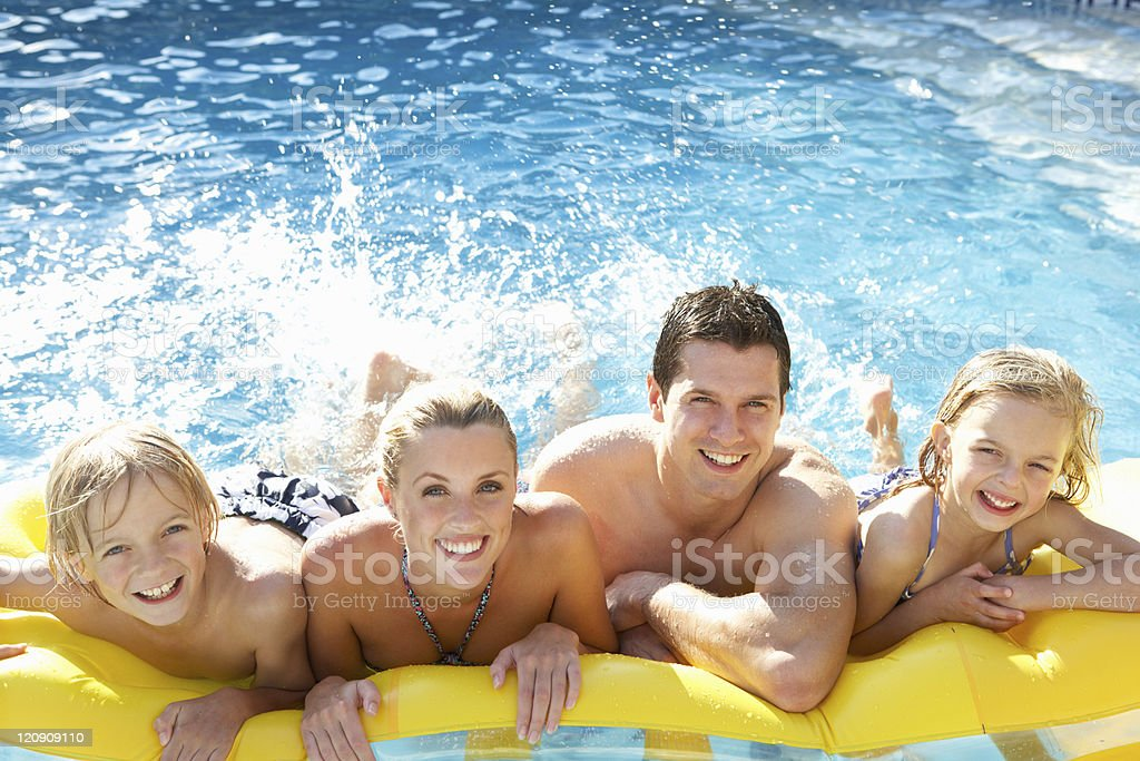 Young family having fun together in pool royalty-free stock photo