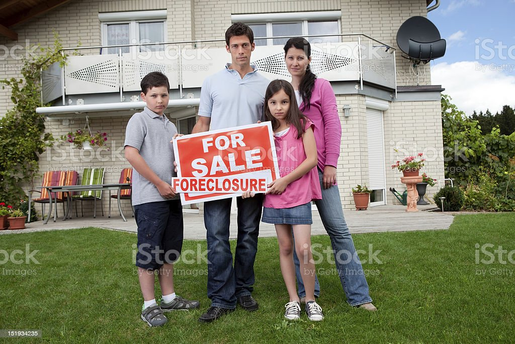 Young family holding a foreclosure sign stock photo