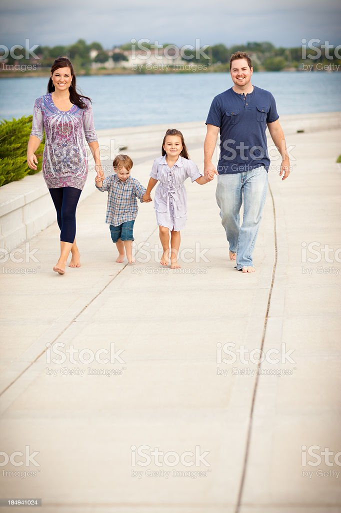 Young Family Holding Hands and Walking Outside, With Copy Space royalty-free stock photo