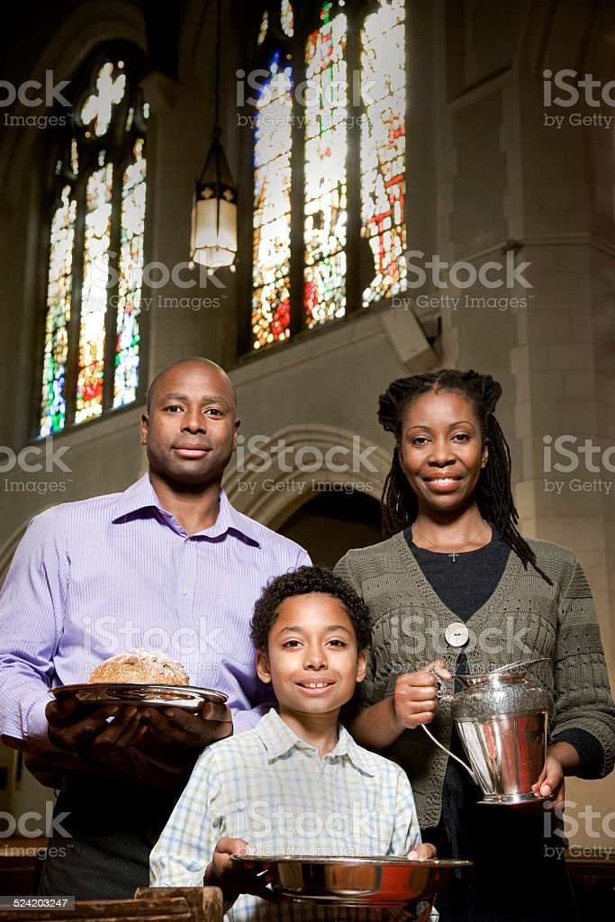 Young Family in Church Aisle With Bread and Wine stock photo