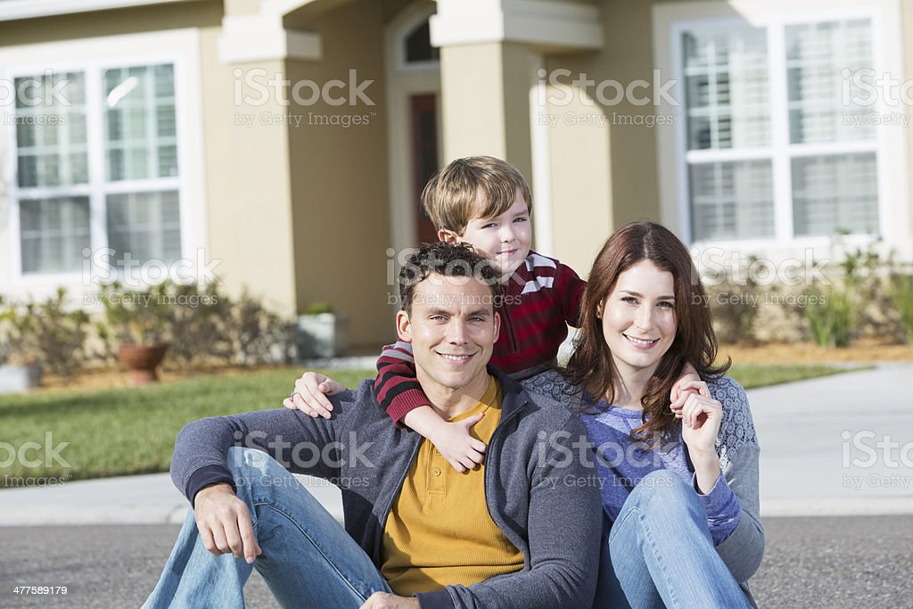 Young family in front of home stock photo