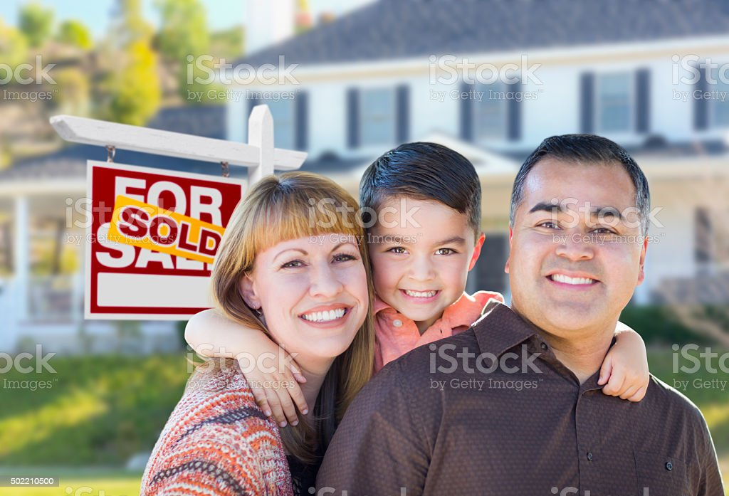 Young Family in Front of Sold Real Estate Sign House stock photo