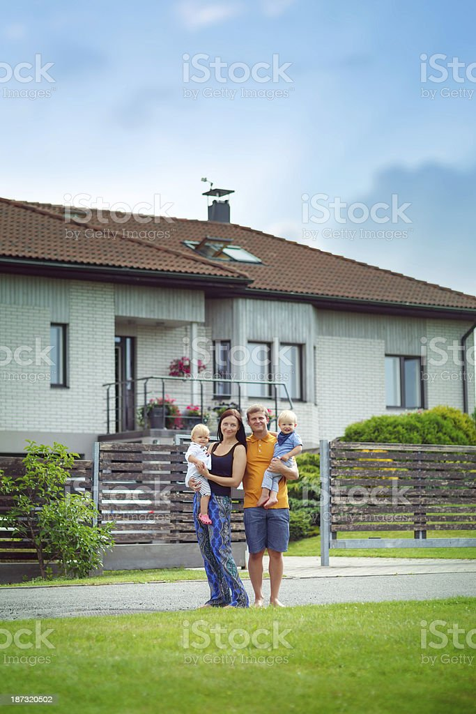 Young family in front of their house stock photo