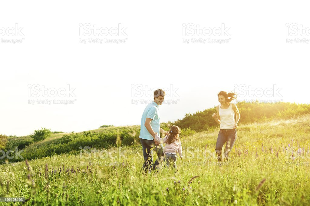 Young family in meadow with lens flare stock photo