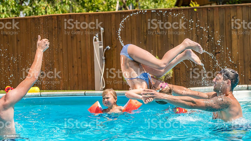 Young family in the pool stock photo
