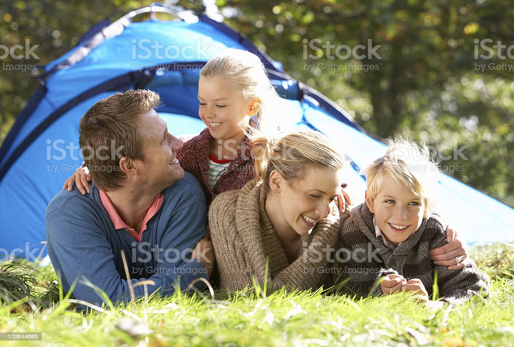 Young family laying outside tent royalty-free stock photo