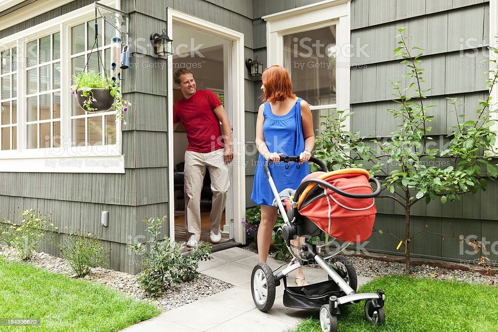 Young Family Leaving Home with Baby Stroller royalty-free stock photo