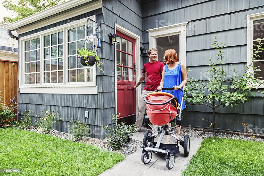 Young Family Leaving Home with Baby Stroller stock photo
