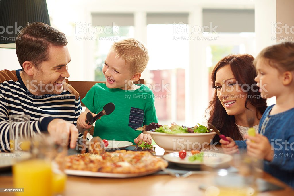 young family mealtime stock photo