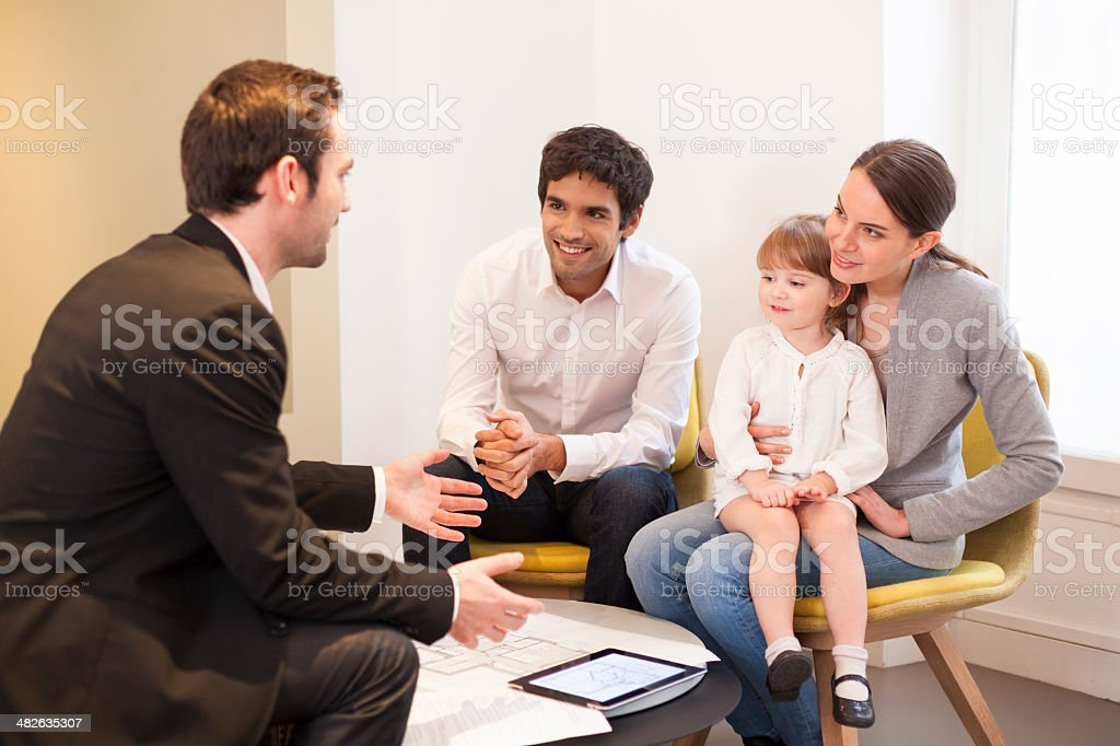 Young Family meeting real-estate agent to buy property stock photo