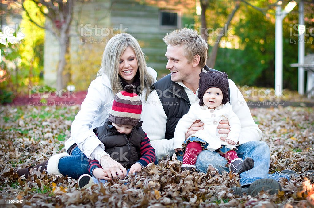 Young Family of Four in Leaves stock photo