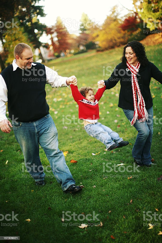 Young Family of Three Playing in an Autumn Park royalty-free stock photo