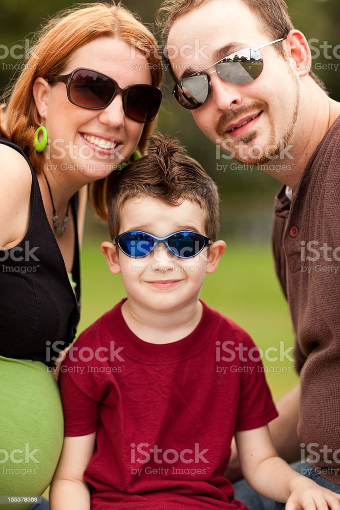 Young Family of Three Wearing Sunglasses While Standing Together Outside royalty-free stock photo