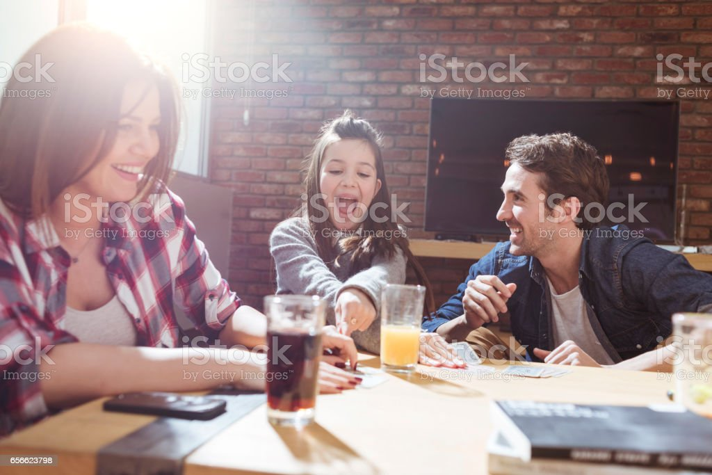 young family playing card games stock photo