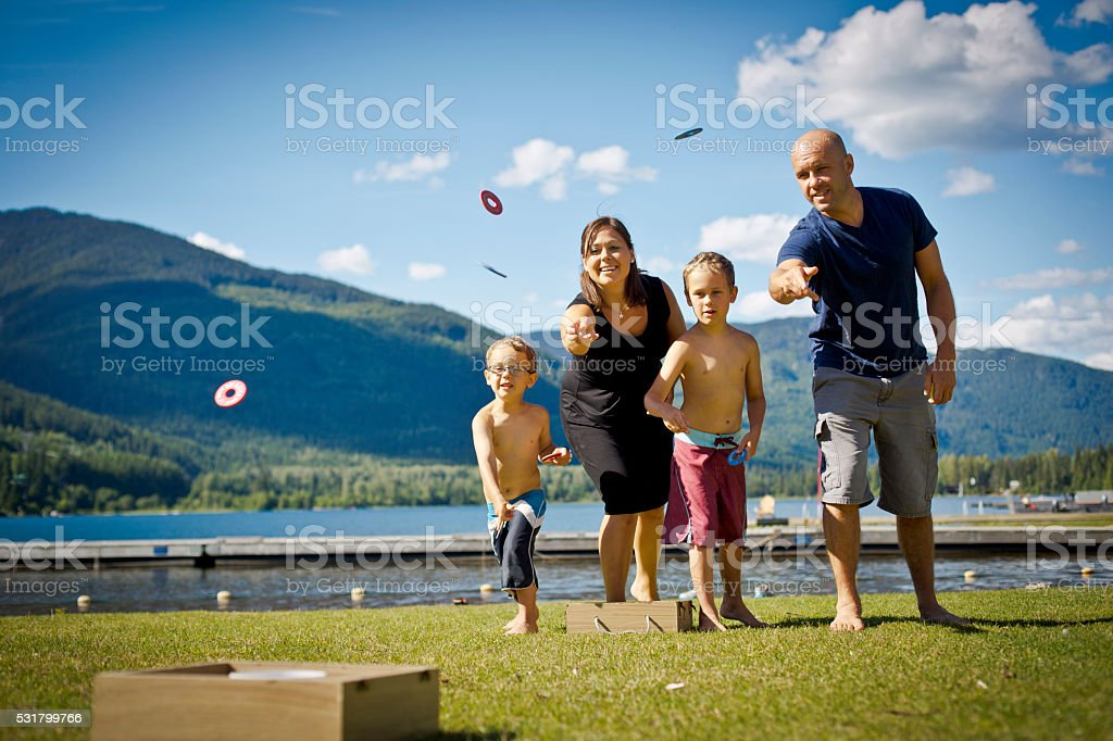 Young family playing game and laughing in park. stock photo
