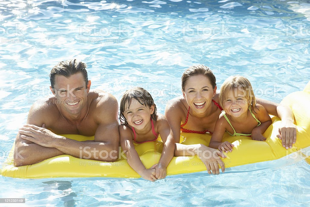 Young family playing in pool stock photo