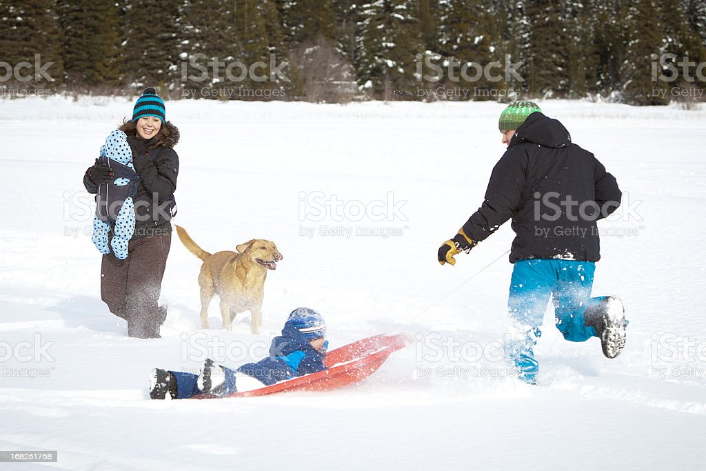 young family playing outside in the snow. royalty-free stock photo