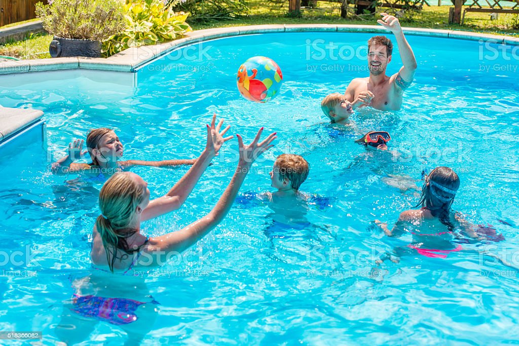 Young family playing with a ball in the pool stock photo