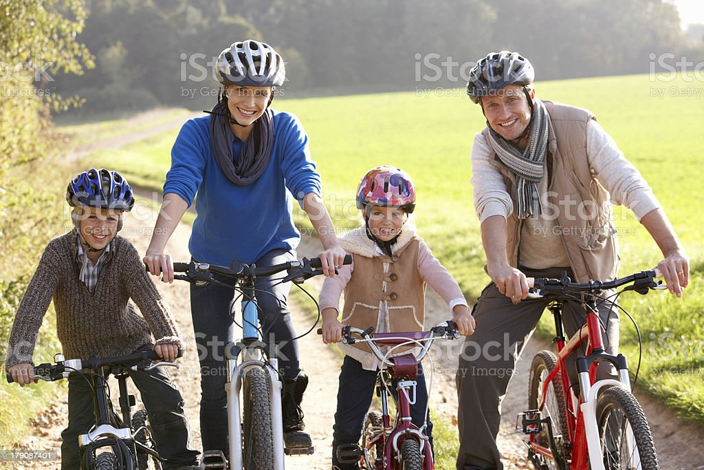 Young family pose with bikes in park royalty-free stock photo