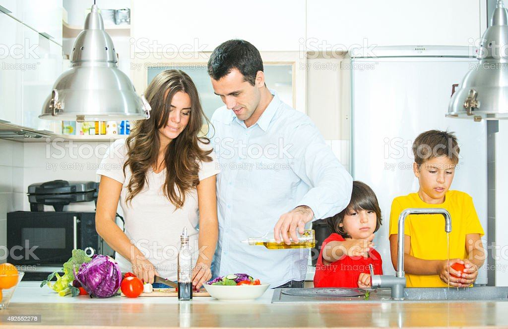 Young family preparing food in kitchen. stock photo