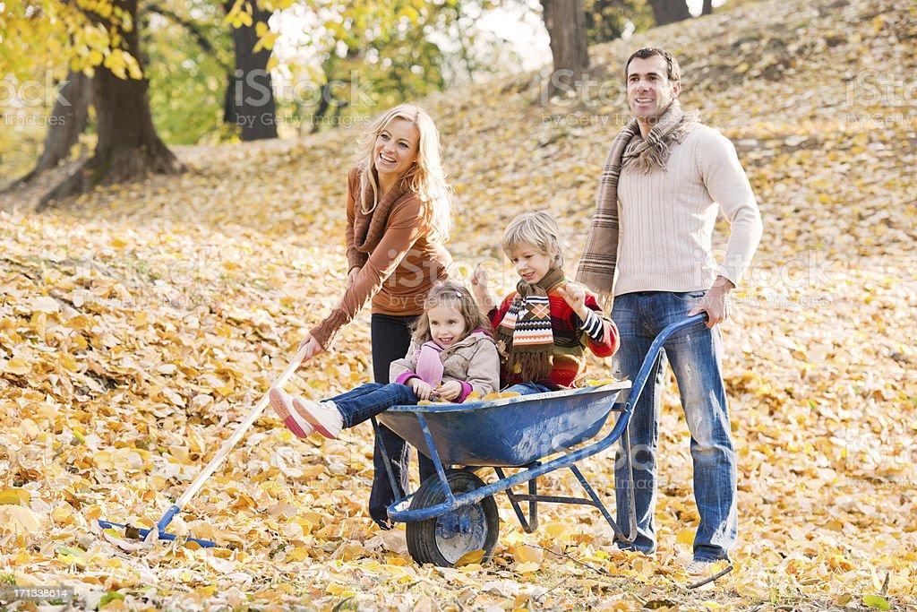 Young family raking leaves. stock photo