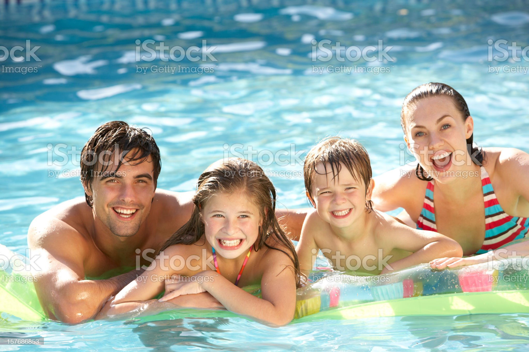 Young Family Relaxing In Swimming Pool royalty-free stock photo
