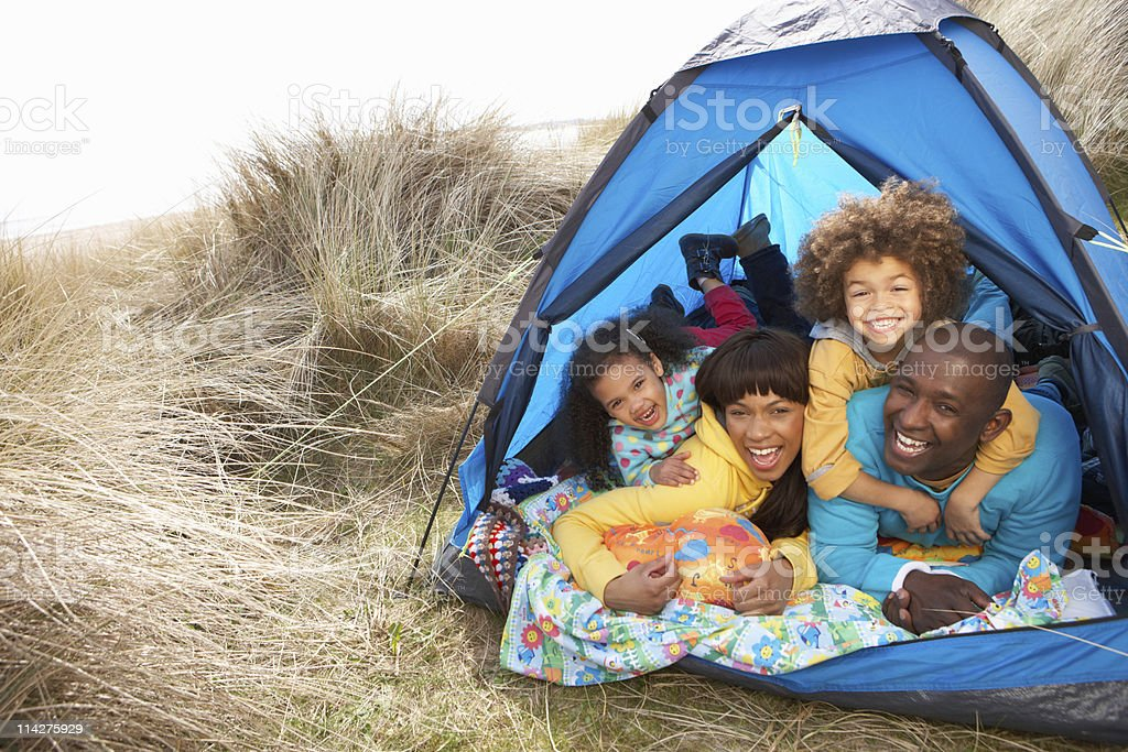 A young family relaxing inside blue tent on camping holiday royalty-free stock photo