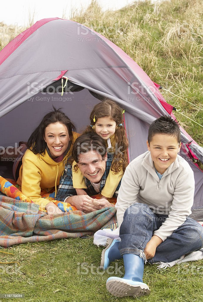 Young Family Relaxing Inside Tent On Camping Holiday royalty-free stock photo