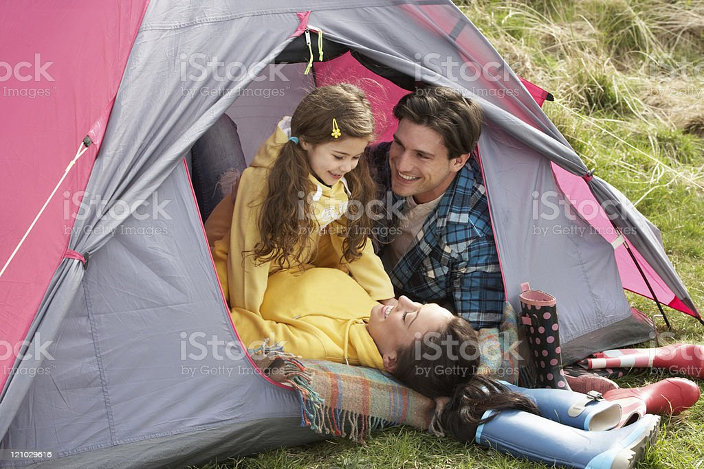 Young Family Relaxing Inside Tent On Camping Holiday stock photo