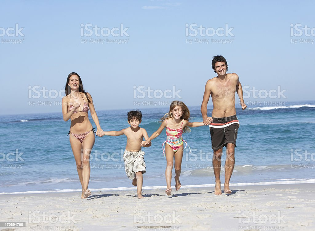 Young Family Running Along Beach on Holiday royalty-free stock photo