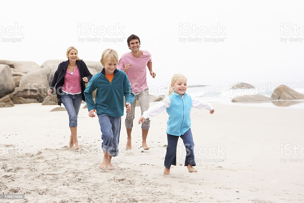 Young Family Running Along Winter Beach royalty-free stock photo