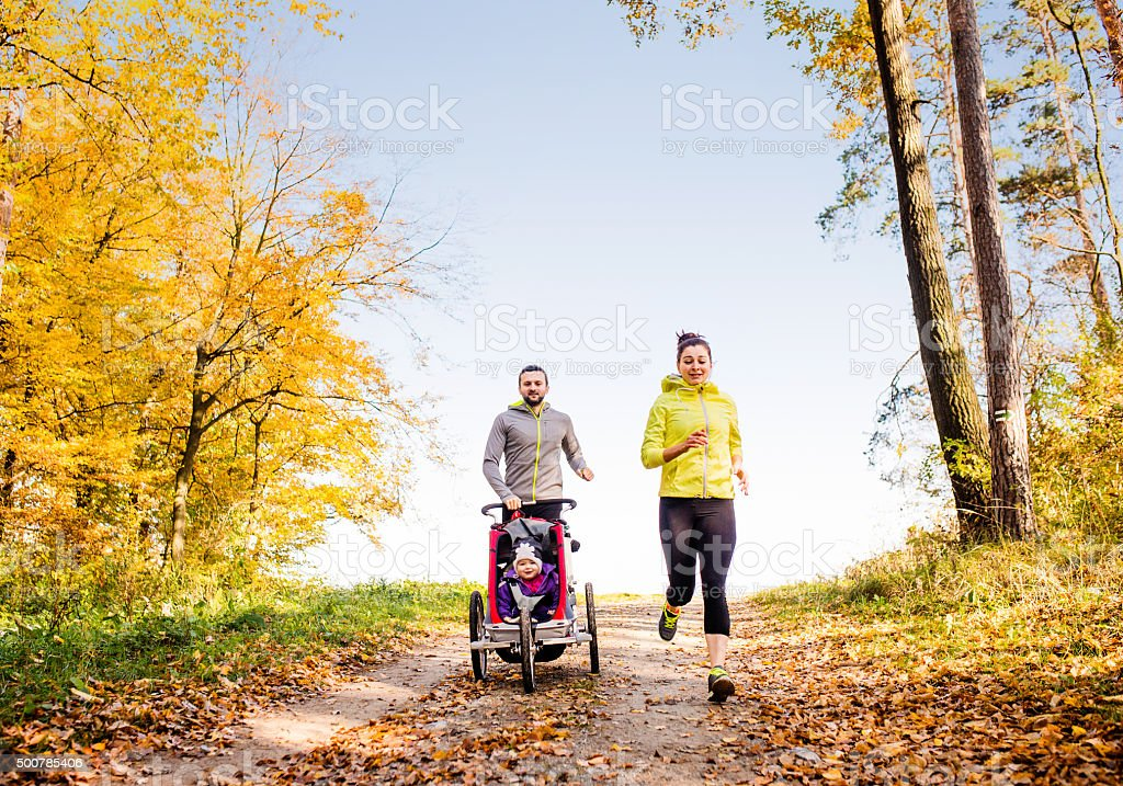 Young family running stock photo