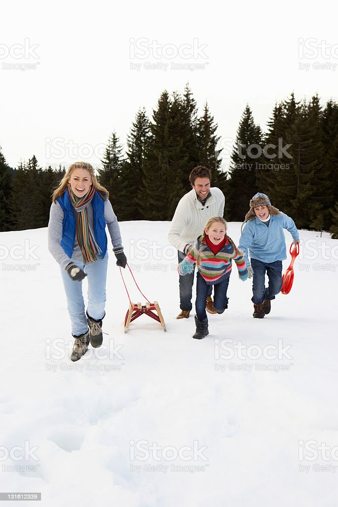 Young Family Running Through Snow With Sled stock photo