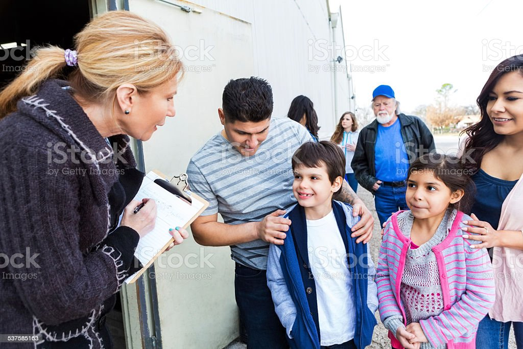 Young family signing up to volunteer at community charity stock photo