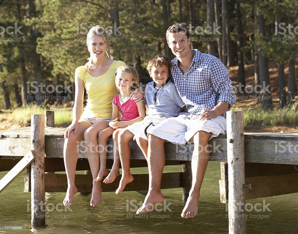Young family sitting by lake royalty-free stock photo
