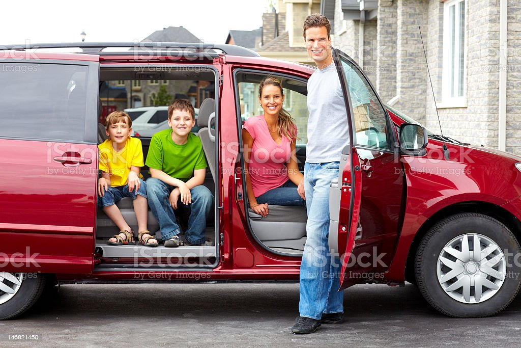 Young family sitting in red SUV and smiling royalty-free stock photo