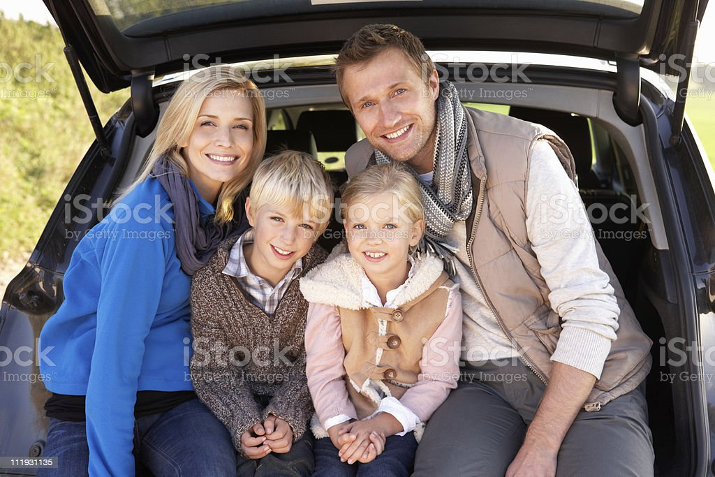 Young family sitting in trunk of car royalty-free stock photo