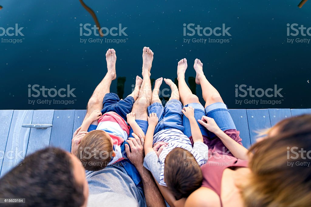 Young family sitting on edge of dock in marina stock photo