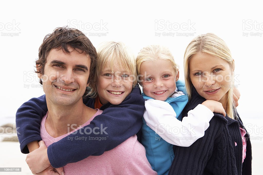 Young Family Sitting On Winter Beach royalty-free stock photo