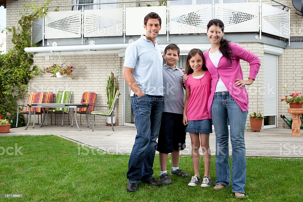 Young family standing in front of their house royalty-free stock photo