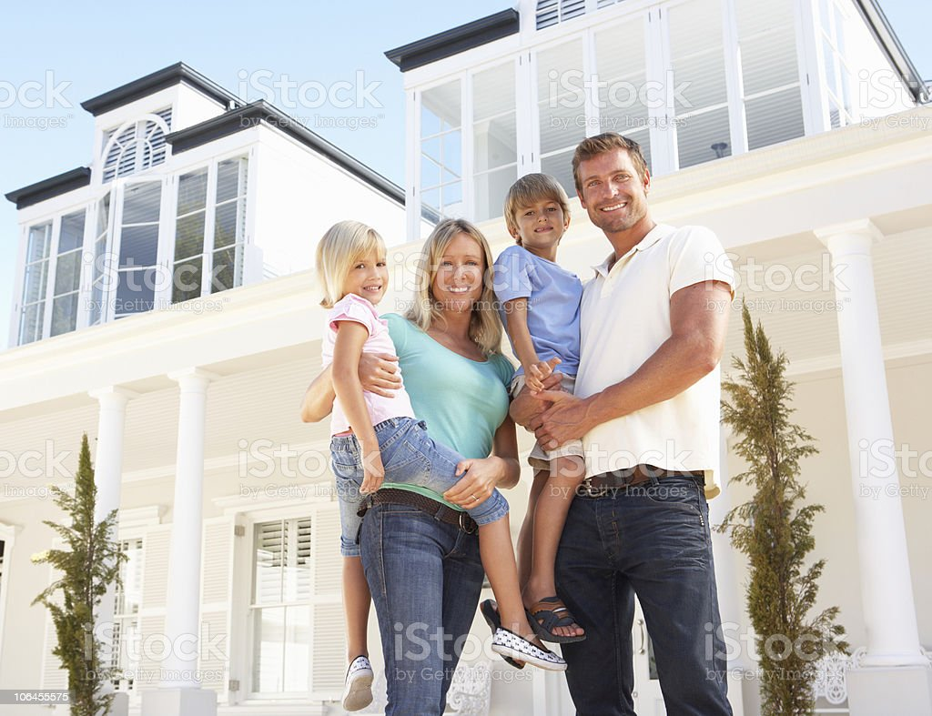 Young Family Standing Outside Dream Home stock photo