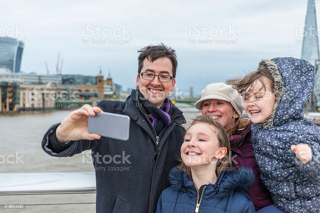 Young Family Taking Vacation Selfie Photo in London as Tourists stock photo