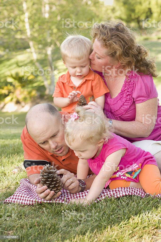 Young Family Talking about Pine Cones in Park royalty-free stock photo
