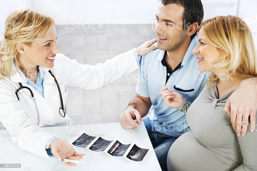 Young family visiting a doctor, looking at Ultrasound. stock photo