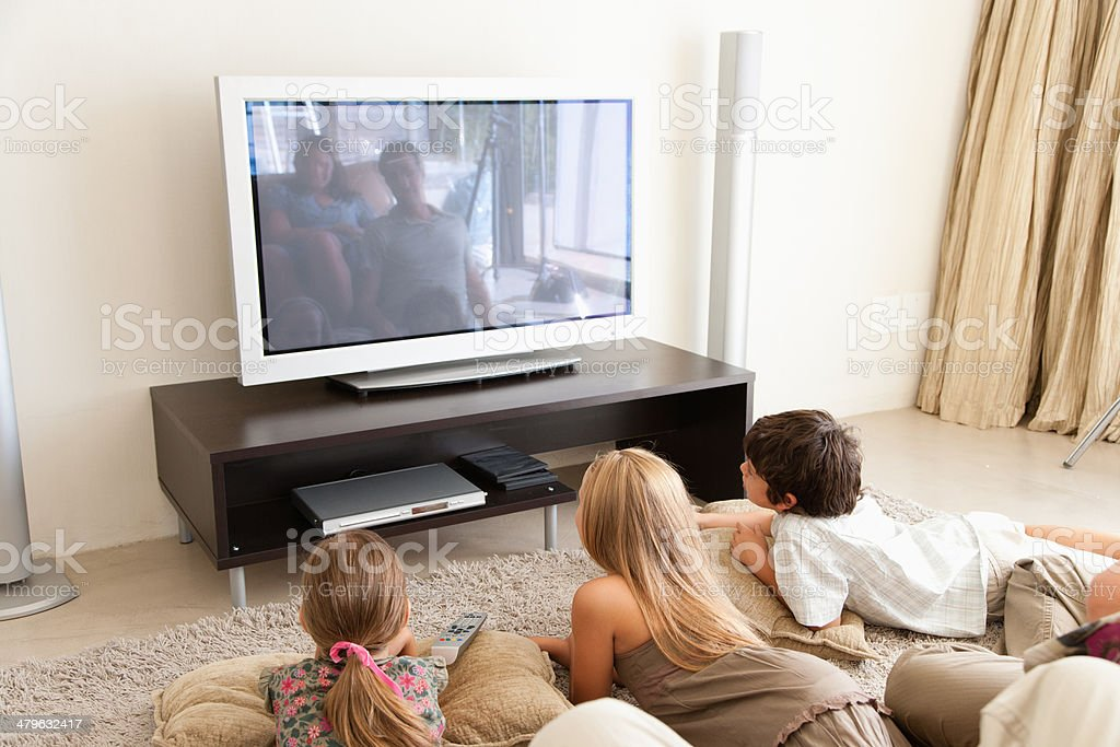 A young family watching television stock photo