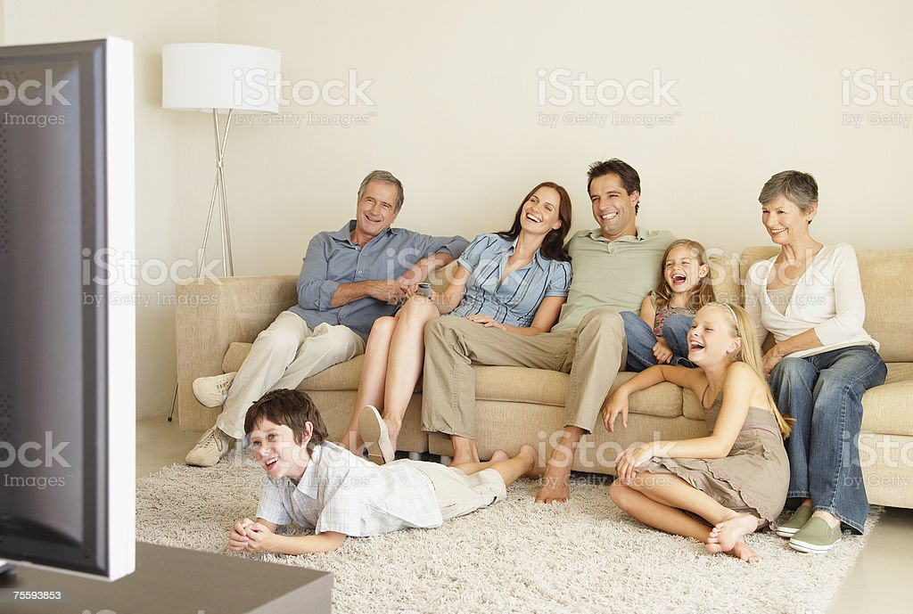A young family watching television with grandparents royalty-free stock photo