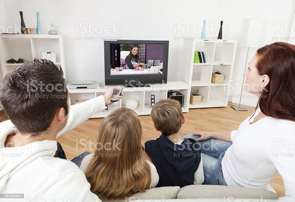 Young family watching TV at home stock photo