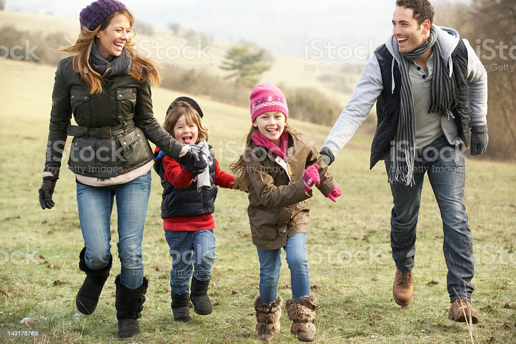 Young family with a boy & girl smiling in winter countryside royalty-free stock photo