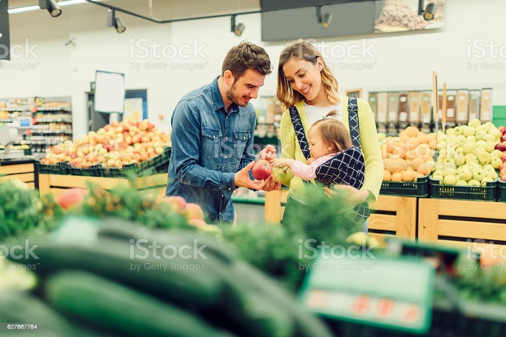 Young Family With Their Baby Daughter Groceries Shopping stock photo